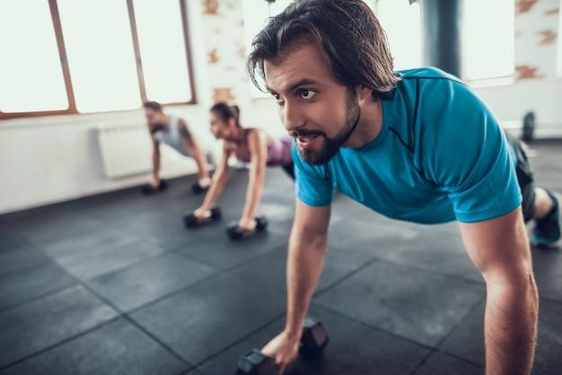 Dois homens e mulher fazendo push ups em halteres.