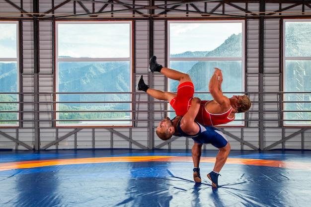 Dois homens em collants de luta livre de esportes e luta livre durante uma luta greco-romana tradicional em luta em uma esteira de luta livre