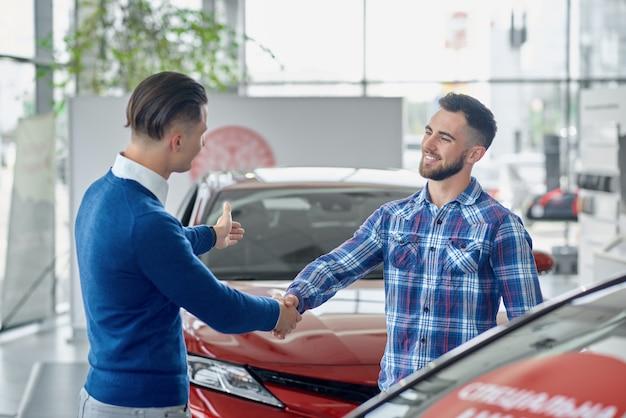 Dois homens em pé no salão entre carros e apertando as mãos.