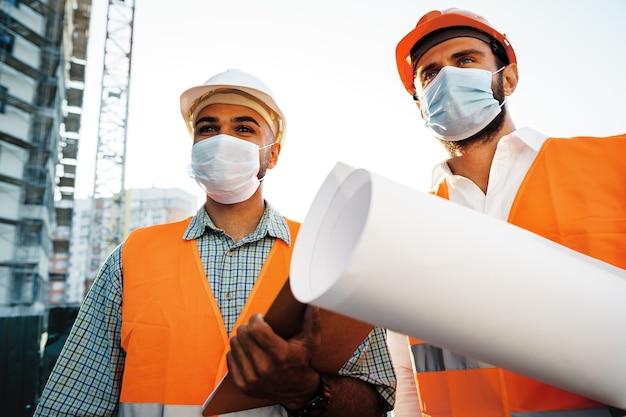 Dois homens em trajes de trabalho e máscaras médicas trabalhando com plantas no objeto