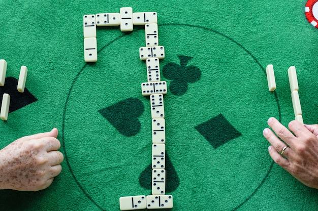 Dois homens em um jogo de dominó, as peças dispostas no centro da mesa.