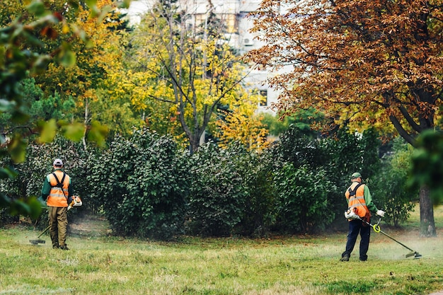Dois homens em um parque cortando grama com cortadores de grama.