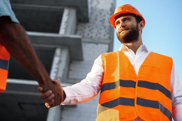 Dois homens engenheiros em traje de trabalho apertando as mãos contra o canteiro de obras