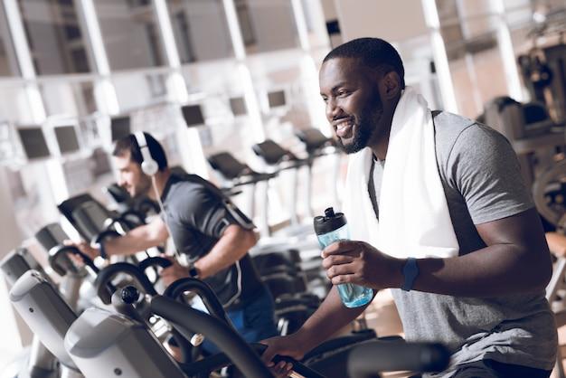 Dois homens estão envolvidos nas esteiras no ginásio moderno.