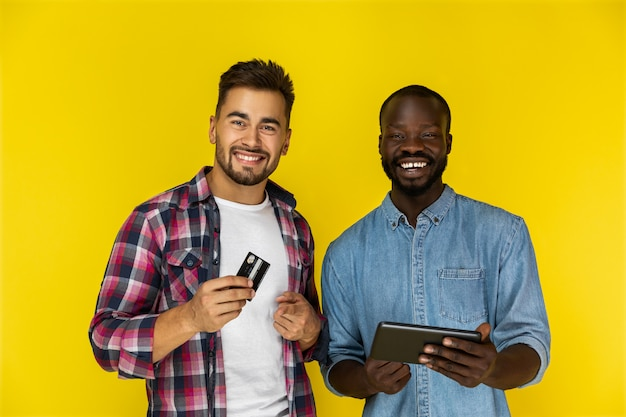 Dois homens estão felizes em usar cartão e tablet
