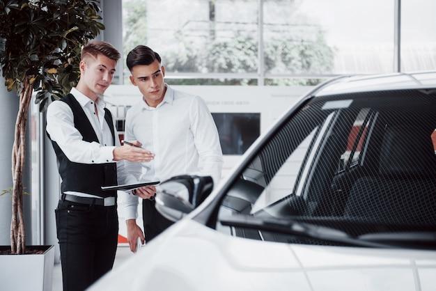 Dois homens estão no showroom contra carros. close de um gerente de vendas em um terno que vende um carro para um cliente. o vendedor dá a chave ao cliente.