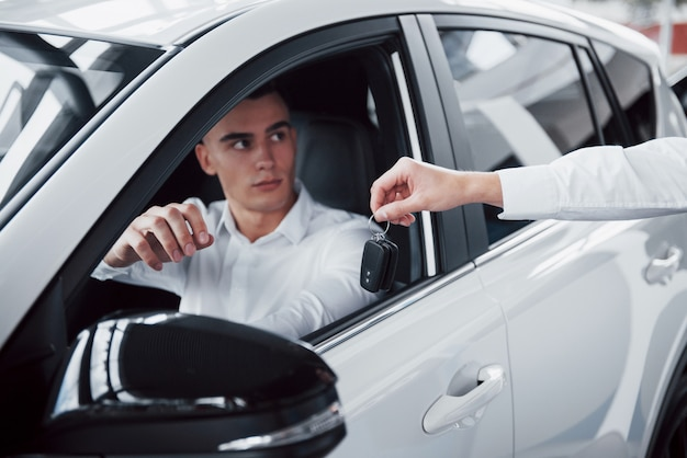 Dois homens estão no showroom contra carros. close-up de um gerente de vendas em um terno que vende um carro para um cliente. o vendedor entrega a chave ao cliente.