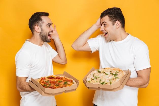 Dois homens europeus solteiros de 30 anos em camisetas brancas sorrindo e segurando caixas de pizza em pé, isolados sobre a parede amarela