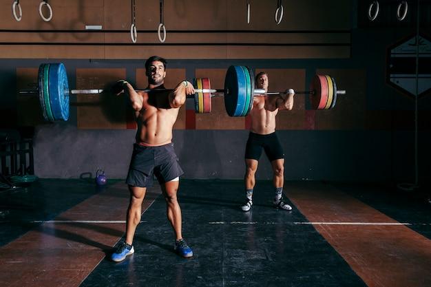 Dois homens fazendo musculação