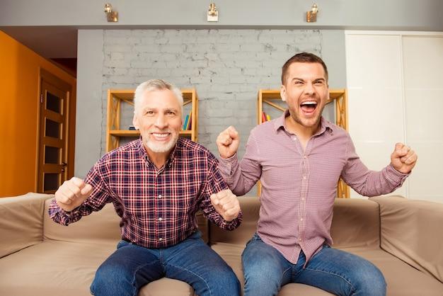 Dois homens felizes assistindo futebol em casa com as mãos levantadas