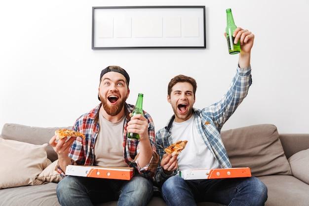 Dois homens felizes com camisas casuais comendo pizza e bebendo cerveja, enquanto assistem a uma partida de futebol em casa