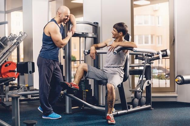 Dois homens felizes discutem o treino de fitness de hoje.