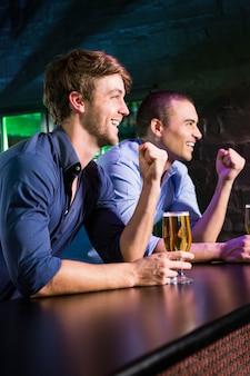 Dois homens felizes, levantando o punho enquanto toma cerveja no balcão de bar em bar