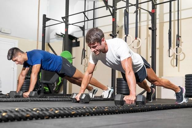 Dois homens fortes fazendo flexões na academia