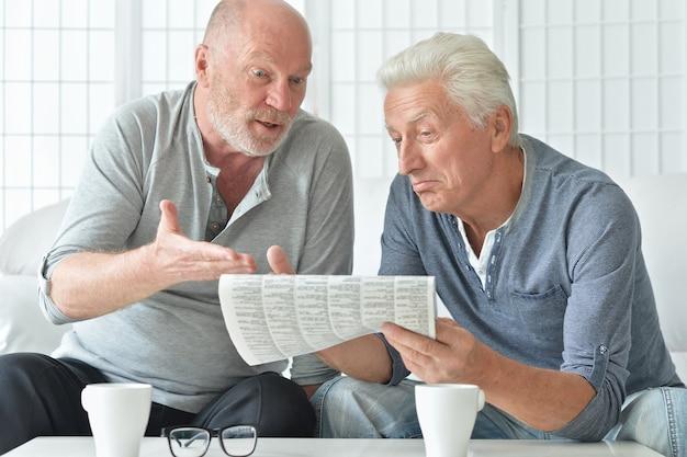 Dois homens idosos com jornal e chá em casa