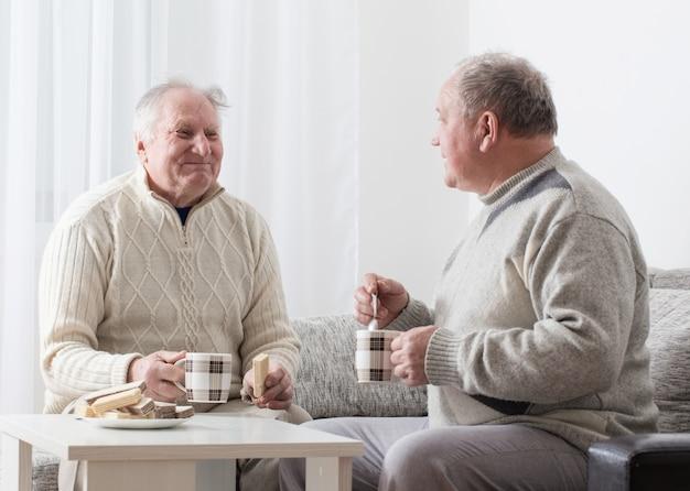 Dois homens idosos com uma xícara de chá interior
