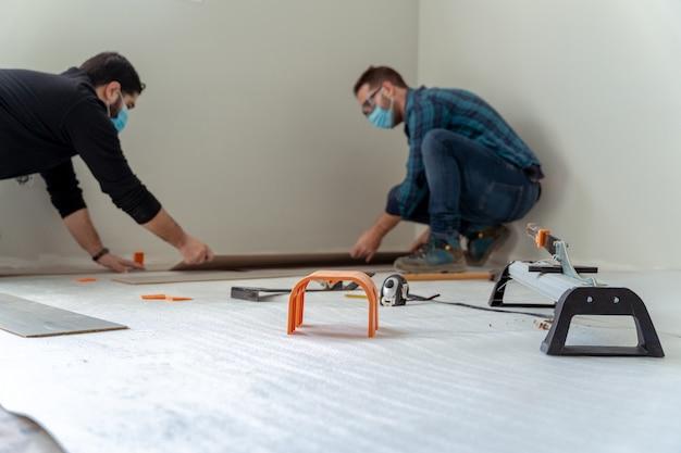 Dois homens instalando um piso de madeira