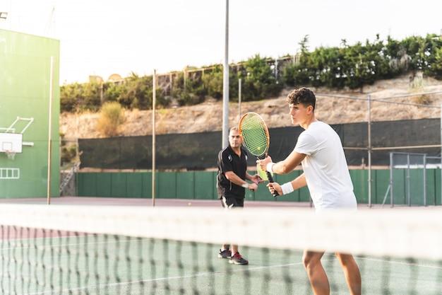 Dois homens jogando tênis em equipe ao ar livre