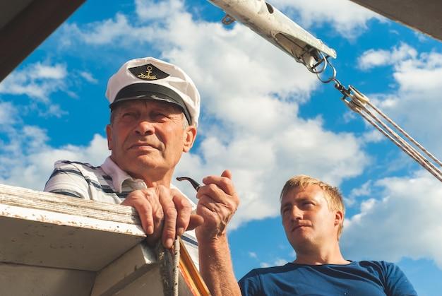 Dois homens, jovens e mais velhos, a bordo de um veleiro