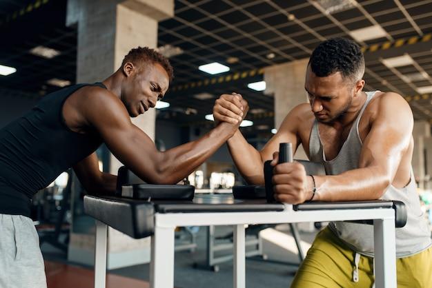 Dois homens lutando em suas mãos, treinamento de queda de braço no ginásio.