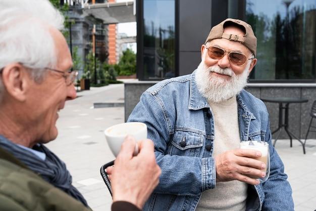 Dois homens mais velhos na cidade tomando café juntos e conversando