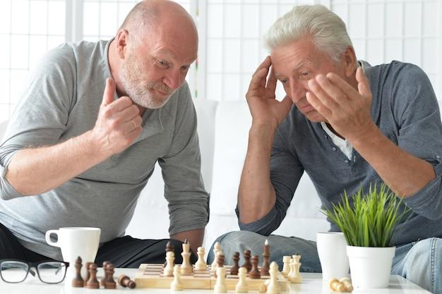 Dois homens mais velhos se divertindo e jogando xadrez em casa