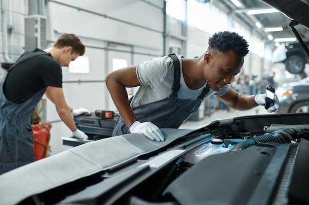 Dois homens mecânicos inspecionam o motor na oficina mecânica.