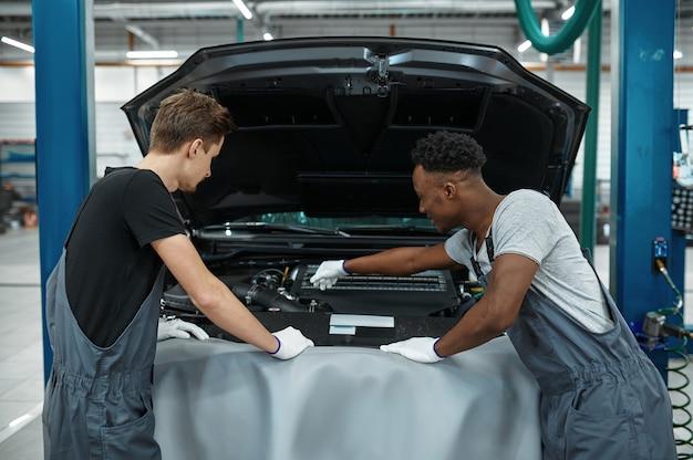 Dois homens mecânicos verificando o motor na oficina mecânica.