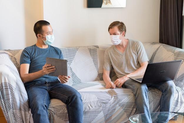 Dois homens multiétnicos com máscara como amigos usando tecnologia e conversando em quarentena em casa