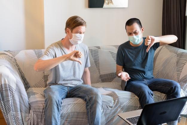 Dois homens multiétnicos estressados usando máscaras de amigos e dando sinal de negativo enquanto fazem videochamadas em quarentena em casa