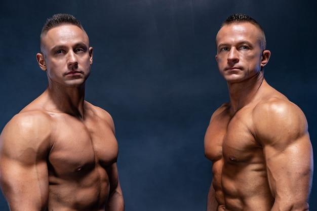 Dois homens musculosos isolado no fundo preto abdômen forte de tronco nu masculino