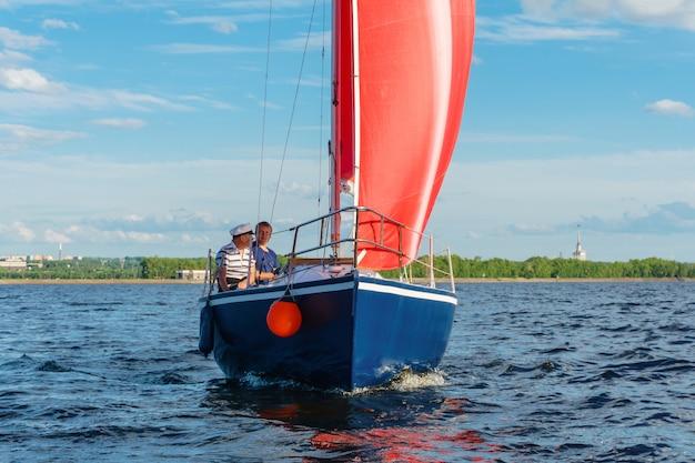 Dois homens navegam em um veleiro com velas vermelhas no lago, tendo como pano de fundo a costa