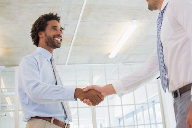 Dois, homens negócios, apertar mão, em, escritório