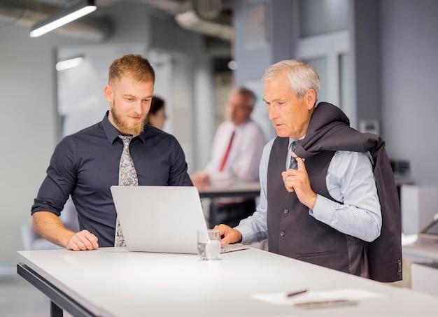 Dois, homens negócios, ficar, perto, a, tabela, olhar, laptop, em, escritório