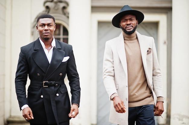 Dois homens negros da moda andando na rua. retrato na moda de modelos masculinos afro-americanos. use terno, casaco e chapéu.