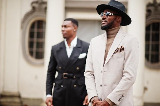 Dois homens negros da moda. retrato na moda de modelos masculinos afro-americanos. use terno, casaco e chapéu.
