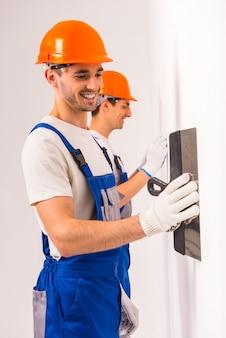 Dois homens putty uma parede branca em um novo apartamento.