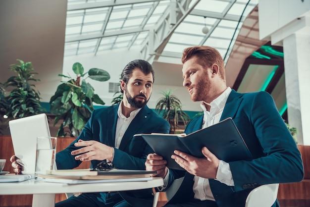 Dois homens que olham a tela do portátil no escritório.