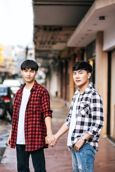 Dois homens que se amam andam de mãos dadas.