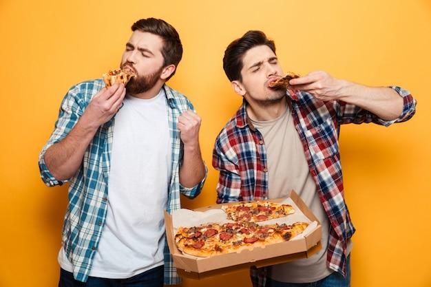Dois homens satisfeitos em camisa comendo pizza na parede amarela