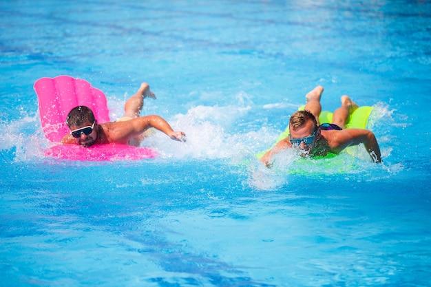 Dois homens se banham na piscina e relaxam