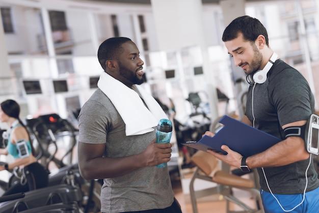 Dois homens se comunicam no ginásio.