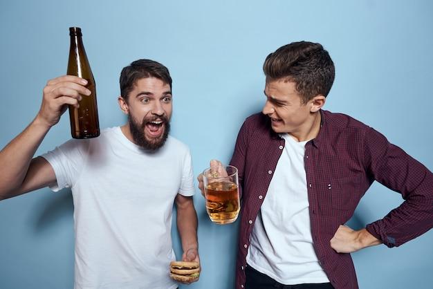 Dois homens se divertem, bebem cerveja e comem fast-food.