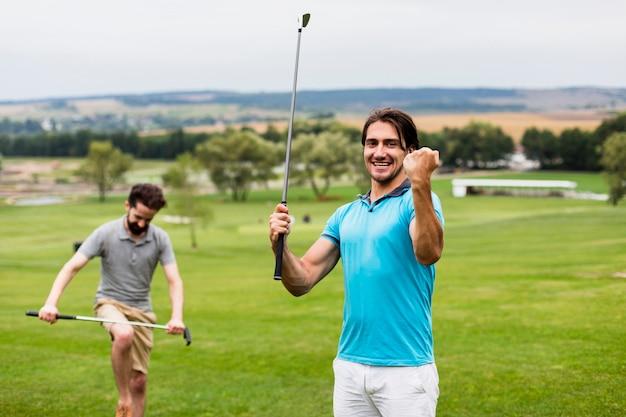 Dois homens se divertindo no campo de golfe