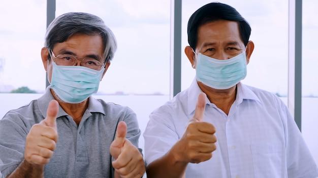 Dois homens sêniors usando máscaras protetoras durante a quarentena em casa.