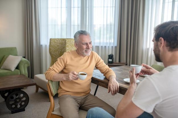 Dois homens sentados à mesa, tomando chá e conversando
