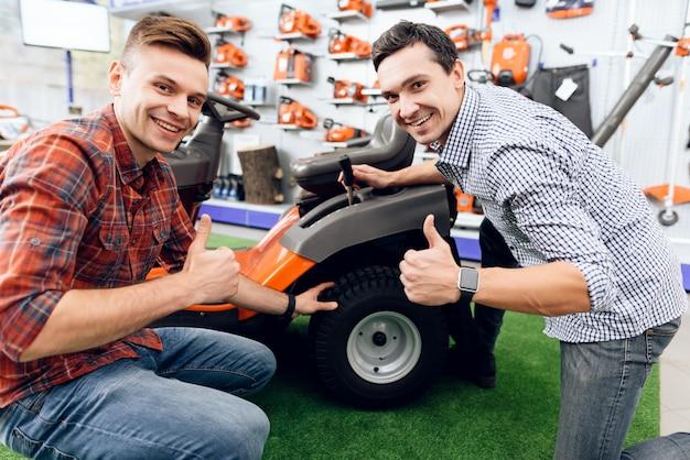 Dois homens sentam-se perto de um cortador de grama e olham para a câmera.