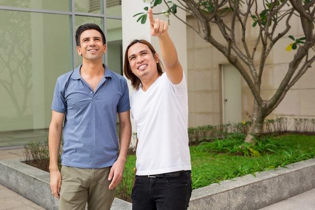 Dois homens sorridentes apontando algo ao ar livre