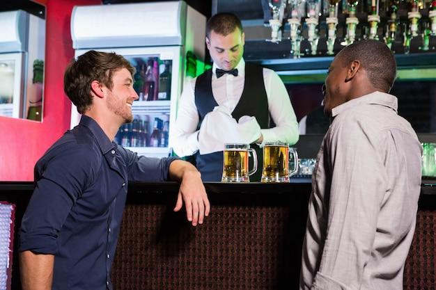 Dois homens sorrindo e conversando enquanto toma cerveja no balcão de bar em bar
