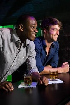 Dois homens sorrindo enquanto tomando uísque no balcão de bar em bar